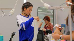 Muotisuunnittelun opiskelija Randa Sabah valmistaa kurssin lopputyönään valkoista bleiseriä.