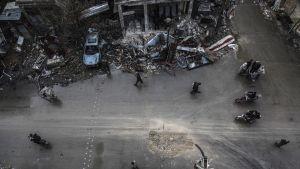 Ylhäältäpäin otettu kuva kadusta. Katu kulkee vaakasuoraan kuvan keskellä. Kuvan yläreunassa näkyy pahoin tuhoutunutta rakennusta ja räjähdyksen repimää tavaraa. Seassa on ainakin yksi tuhoutunut auto. Kuvan alareunassa näkyy myös raunioita. Kadun keskellä näyttäisi olevan jonkinlainen räjähdyskraaterin tapainen, joka on ilmeisesti täytetty. Ihmisiä kävelee ja ajaa moottoripyörillä kadulla.