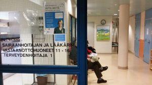 Anonyymejä ihmisiä terveyskeskuksen odotushuoneessa.