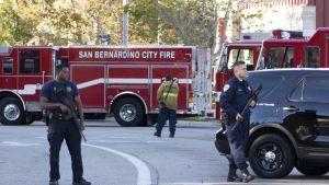 Kaksi aseistettua poliisia seisoo paloautojen edessä.