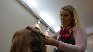 Kampaaja tekee kiharoita hiuksiin.