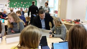 Kuvan keskellä mies seuraa koululaisen työskentelyä. Ympärillä lapsia ja taustalla aikuisia.