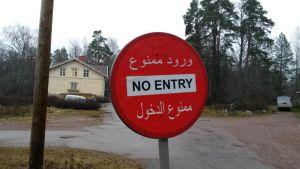 Arabian- ja darinkielistä tekstiä liikennemerkissä talon edustalla.