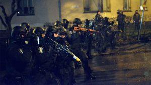 Noin viisitoista erikoisvarusteista poliisia rivissä.