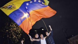 Kolme miestä heiluttaa suurta Venezuelan lippua.