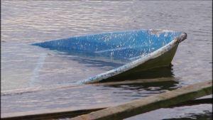 Suurimmaksi osaksi veteen vajonnut pienvene.