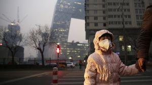 Tyttö käveli kadulla hengityssuojain kasvoillaan Pekingissä 7. joulukuuta.