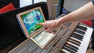 Käsi osoittaa tabletin ruutuun, jossa pianonsoiton opetuspeli