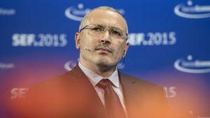 Mihail Hodorkovski katsoo ylävasemmalle. Hänellä on tumma puku ja kravatti. Tausta on sininen. Taustakankaassa näkyy lyhenne SEF 2015, joka tulee sanoista Swiss Economic Forum 2015.