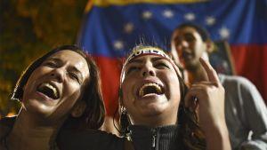 Kaksi naistaa hurmoksessa Venezuelan lippu takanaan.