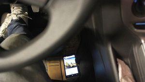 Matkapuhelin auton lattialla, Instagramissa Lamborghinin kuva.