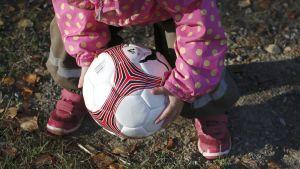 Lapsi nostaa jalkapalloa maasta.