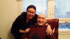 Eino Hautamäki istuu keinutuolissa ja vierellä kummitytär Teija Pokela.