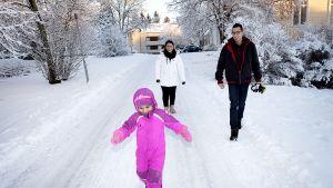 Perhe ulkona lumisessa säässä.