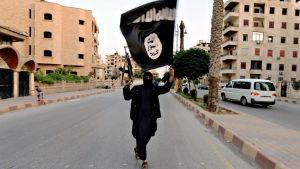 Mustiin pukeutunut aseistaunut henkilö pitelee ISIS-lippua ilmassa.