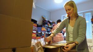 Työntekijä pakkaa lastenvaatteita postipaketteihin.