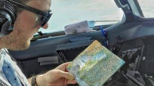 Mies tutkii karttaa lentokoneessa.