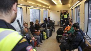 Poliisi tarkasti matkustajien henkilöllisyystodistuksia Tanskan ja Ruotsin välisessä junassa 12. marraskuuta 2015.