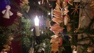 Lähikuvassa joulukuusi. Olkikoristeita, sähkökynttilä ja käpyjä.