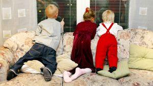 Lapset odottavat joulupukkia ikkunassa.
