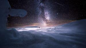Hiihtäjä lumimaisemassa tähtitaivaan alla.