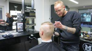 Parturi leikkaa asiakkaan hiuksia.