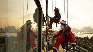 Joulupukiksi pukeutunut mies ikkunanpesutelineellä rakennuksen ulkopuolella.