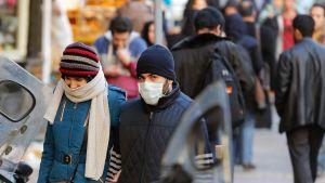 Mies kulkee Teheranin kadulla maski suun peittona.