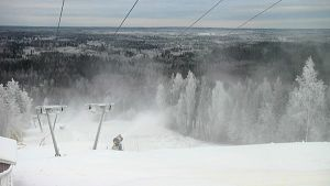 Luminen maisema kuvattu laskettelurinteen huipulta. Lumitykit ovat työssään.