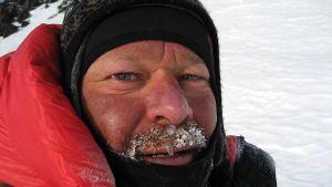 Lähikuva miehen kasvoista. Viikset ovat lumessa ja jäässä.