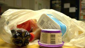 Muovipakkauksia muovipussissa pöydällä.