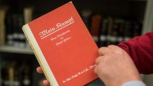 Henkilö pitelee Mein Kampfin ensipainosta Lähihistorian instituutti ifZ:n kirjastossa.