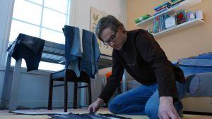 Marko Komulainen asettelee farkkupaloja vierekkäin lattialle.