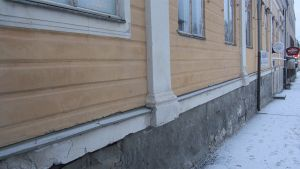 Lähikuvassa osa Raatihuoneenkadulla Pietarsaaressa sijaitsevaa rakennusta. Seinää ja perustusta, kauempana ravintolakylttejä.