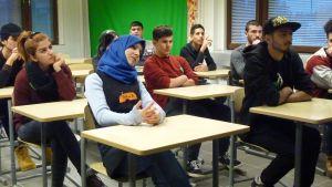 Nuoria turvapaikanhakijoita pulpettien ääressä