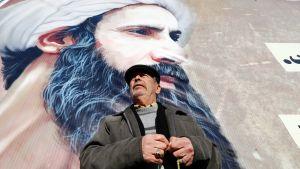 Iranilaismies seisoo shiialaisen uskonoppineen Nimr al-Nimrin julisteen edessä.