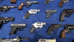 Kuva pistooleista ja revolvereista. Sinisen veran päällä on useita erilaisia aseita, myös yksi pieni konepistooli.
