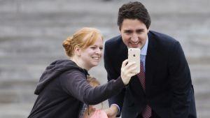 Justin Trudeau ja naiskannattaja katselevat hymyilleen valokuvaa naisen kännykästä. Naista vasten painautuu pieni tyttö.