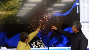 Kaksi miestä osoittelee seinälle heijastetulle kartalle piirrettyjä järistyspisteitä.