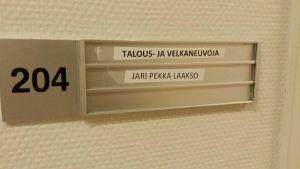 Velkaneuvoja Laakson nimi kyltti toimiston ovella.