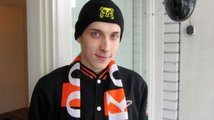 Nuori mies on pukeutunut oranssimustaan KooKoon kannattajapaitaan ja kaulan ympärillä roikkuu jääkiekkojoukkueen fanihuivi,