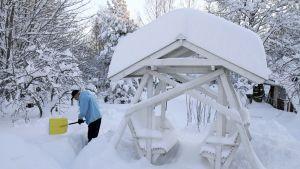 Mies tekee pihallaan lumitöitä.