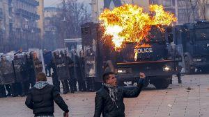 mellakkapoliiseja, poliisiauto tulessa ja mielenosoittajia