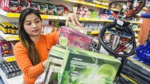 Yupaporn Nanthajak asettelee makutupakoita Siam Flower-kaupassa Kuopiossa.