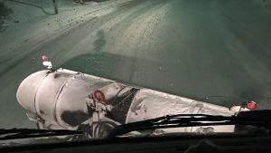 Näkymä lumiauran ohjaamosta lumiselle ajotielle.