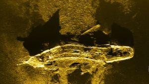 Laivan hylky meren hiekkapohjassa ylhäältäpäin kuvattuna.