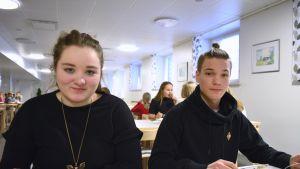 opiskelijat syövät kouluruokaa ja katsovat kameraan