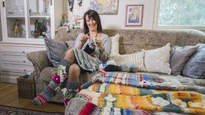 Nainen neuloo villasukkaa sohvalla.