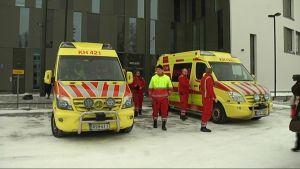 Ambulanssieja ja henkilöstöä poliisiasema Miekkalinnan pihassa