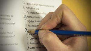 Lukuhaasteen vaihtoehtoja ruksataan, käsi kirjoittaa rasti ruutuun-menetelmällä.